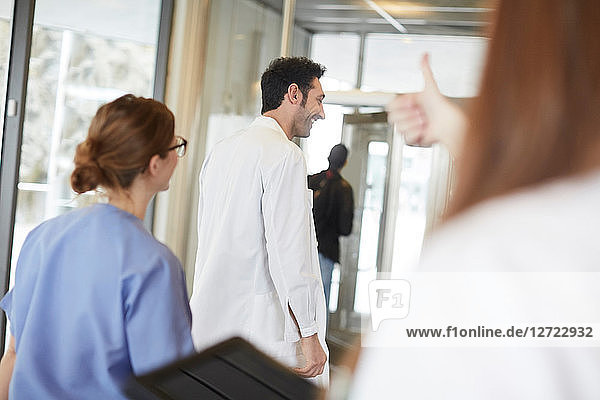 Cropped image of female nurse showing thumbs up to young doctor walking with coworker in lobby at hospital