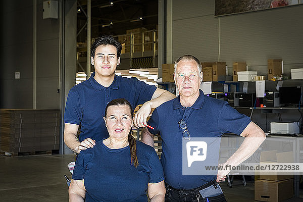 Portrait of confident multi-ethnic workers standing at distribution warehouse