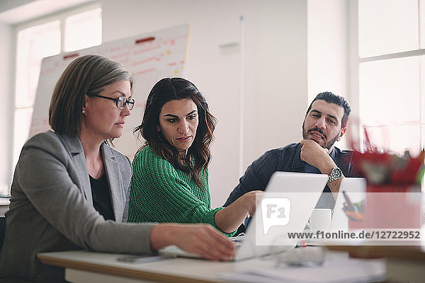 Creative business people discussing over laptop at desk in office
