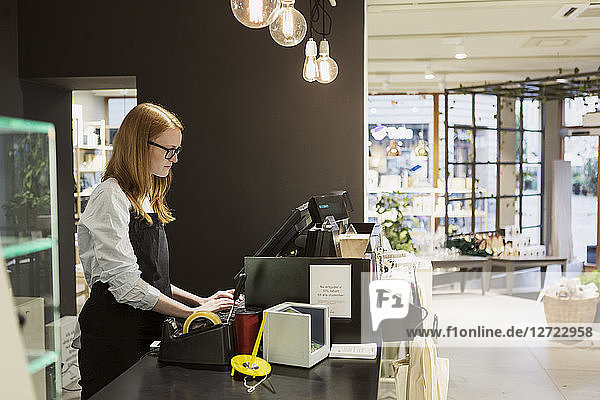 Side view of female owner using computer at checkout counter in design store