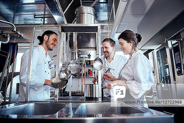 Smiling male and female chefs cooking food in commercial kitchen