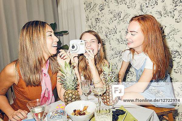 Cheerful young woman holding camera while sitting amidst female friends at home during dinner party