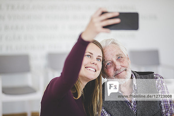 Smiling young woman taking selfie with grandfather while sitting in nursing home