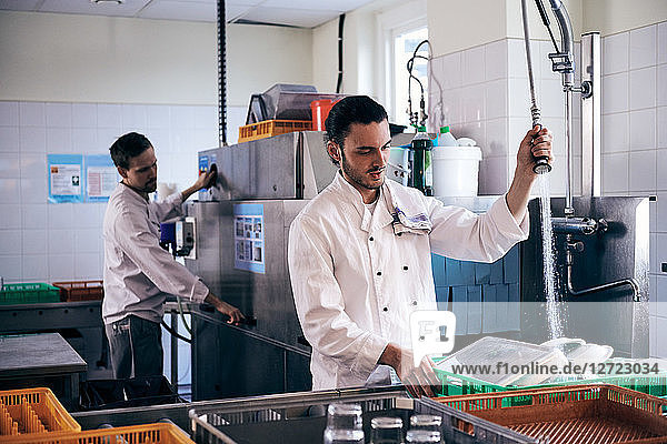 Chef spraying water on plates while colleague working in commercial kitchen
