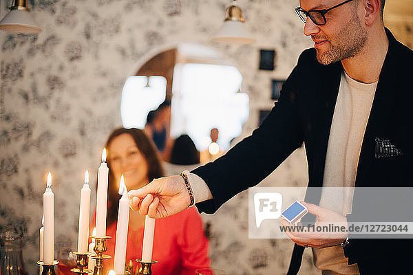 Smiling man igniting candles at dinner party with friend in background