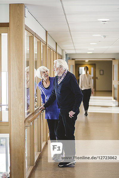 Senior couple talking while standing by window in corridor at nursing home