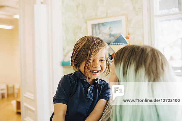 Smiling boy looking at dyed hair teacher in classroom