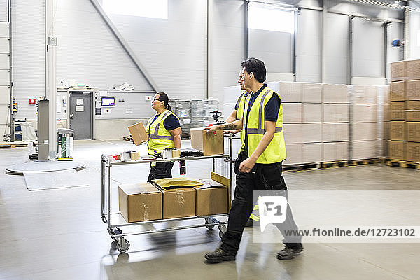 Multi-ethnic coworkers walking while pushing cart at distribution warehouse