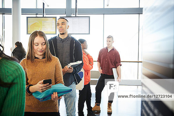 Young male and female students standing in row at university lobby