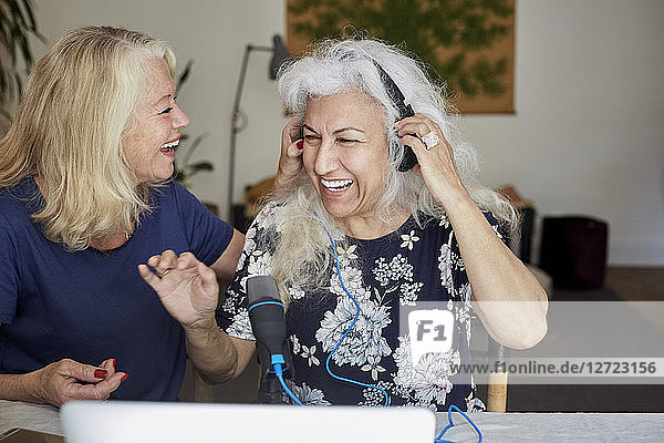 Happy senior women vlogging while sitting at home