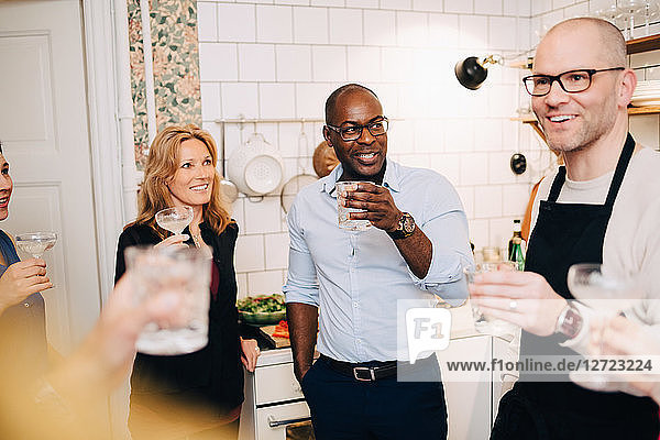 Multi-ethnic mature friends enjoying drinks while talking in kitchen at home