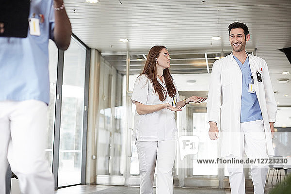 Smiling young healthcare workers discussing while walking in lobby at hospital