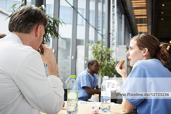 Mature doctor talking with mid adult female nurse while sitting at table in hospital cafeteria