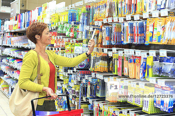 France  woman in a supermarket.School items.
