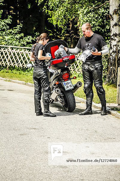 Motorcyclist and his pillion passenger stop at the roadside to enjoy a picnic in the Austrian Alps.
