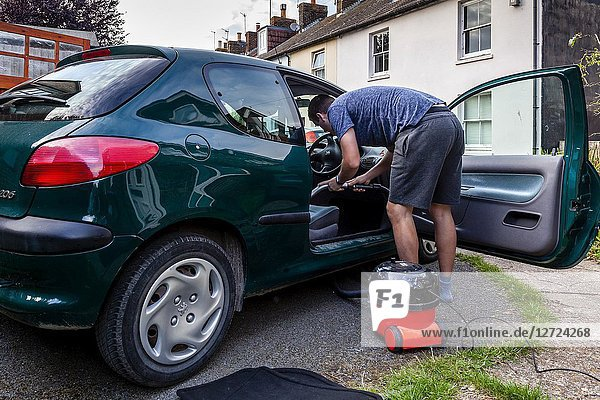 A Young Man Vacuum Cleans His Car  Sussex  UK.