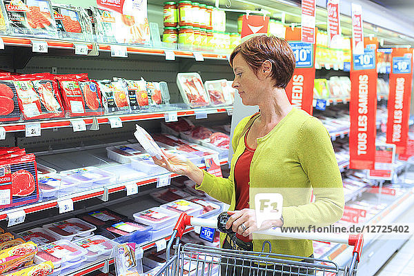 France  woman in a supermarket. Meat department.