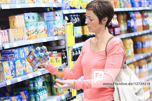 France  woman in a supermarket dividing products batch.