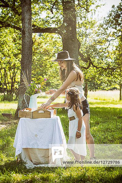 Young mother and daughter during a brunch in the country. Mandatory credit: Design culinaire : food-design-studio.fr