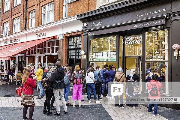 United Kingdom Great Britain England  London  Kensington  Vendi  gelateria  ice cream gelato shop  store window  line  queue  man  woman  Muslim  busy