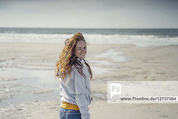 Redheaded woman relaxing on the beach  laughing