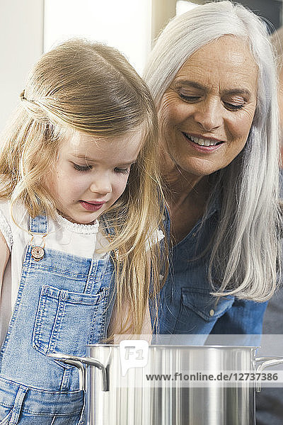 Grandmother and granddaughter cooking together  looking at pot