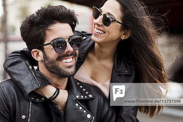Portrait of happy young couple wearing sunglasses and leather jackets