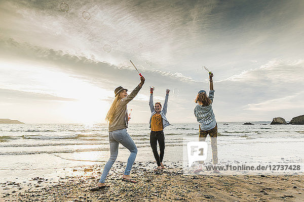 Happy friends making soap bubbles on the beach