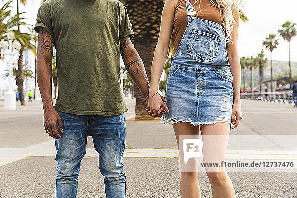 Spain  Barcelona  multicultural young couple holding hands on promenade  partial view
