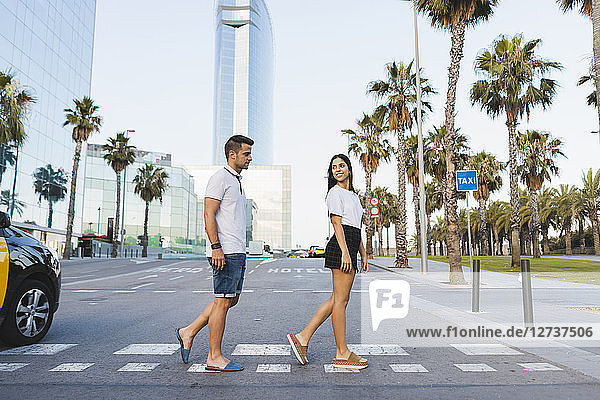 Young couple crossing street in the city  flirting