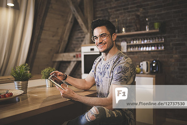 Portrait of smiling young man using tablet in kitchen at home