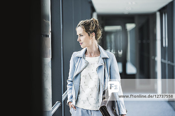 Businesswoman looking out of window in office passageway