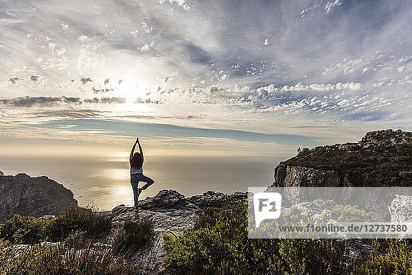 South Africa  Cape Town  Table Mountain  woman doing yoga on a rock at sunset