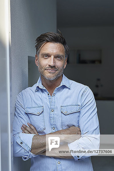 Portrait of smiling man wearing light blue denim shirt