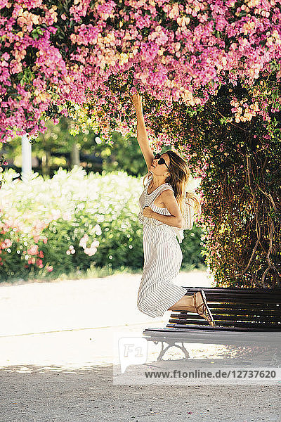 Woman reaching for pink blossoms in park