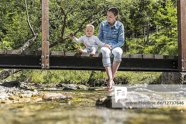 Mother and daughter sitting on wooden bridge  girl throwing stone into mountain stream