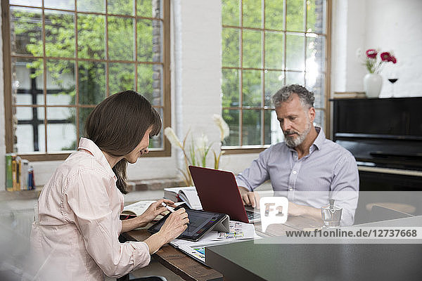 Mature couple working from their home office  using laptop and digital tablet