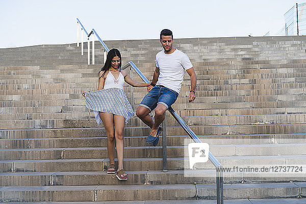 Young couple walking down stair  man sliding on railing