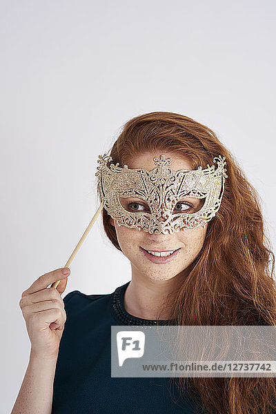 Portrait of smiling redheaded woman with masquerade mask
