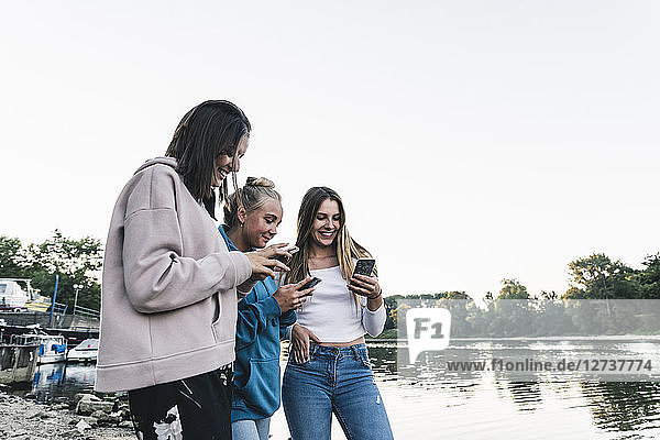 Three young women using cell phones at the riverside