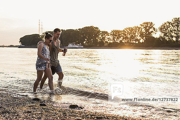 Happy young couple wading in river at sunset