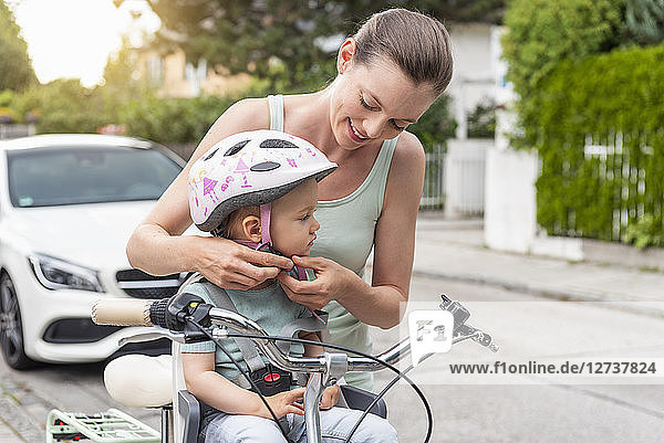 Mother and daughter  daughter wearing helmet sitting in children's seat