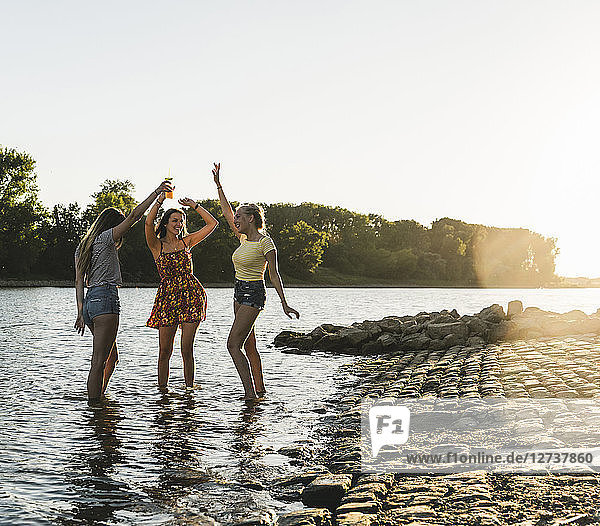 Three happy young women in a river at sunset