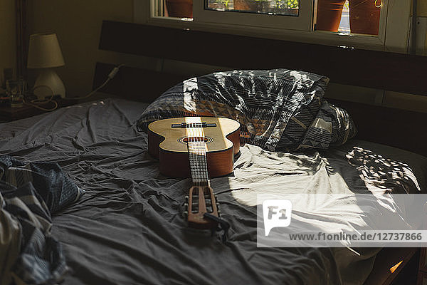 Acoustic guitaron top of a bed with sunlight coming through the window