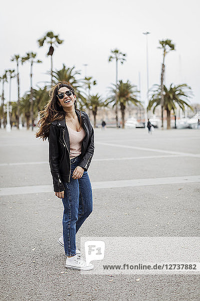 Spain  Barcelona  happy young woman standing on promenade with palms