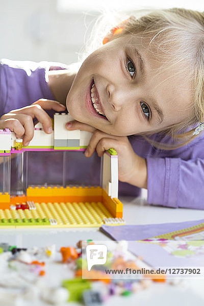 Portrait of happy little girl playing with building bricks