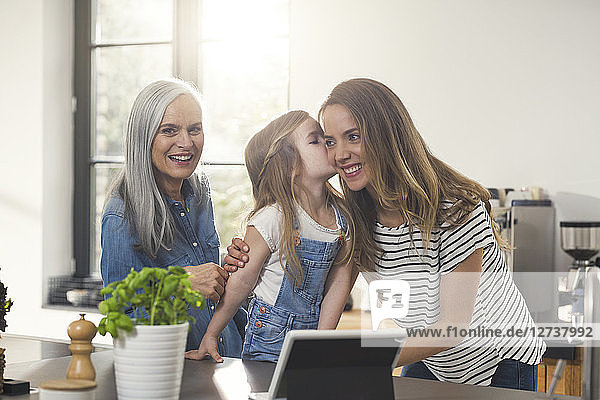 Girl kissing mother  grandmother watching