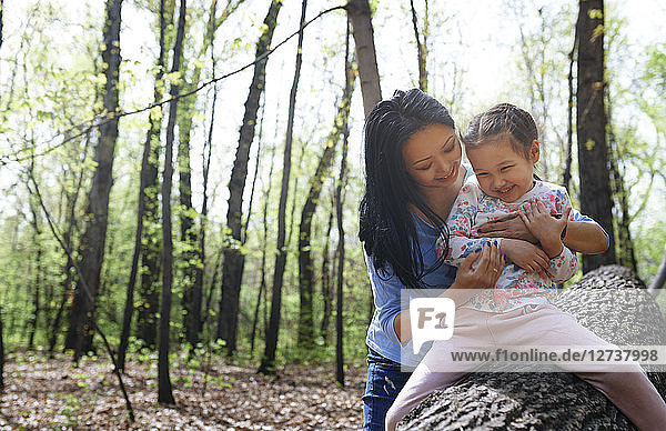 Mother and daughter in park  sitting on tree trunk