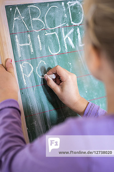 Back view of girl writing alphabet on chalkboard