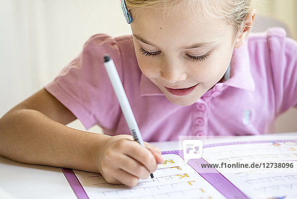 Smiling little girl writing alphabet